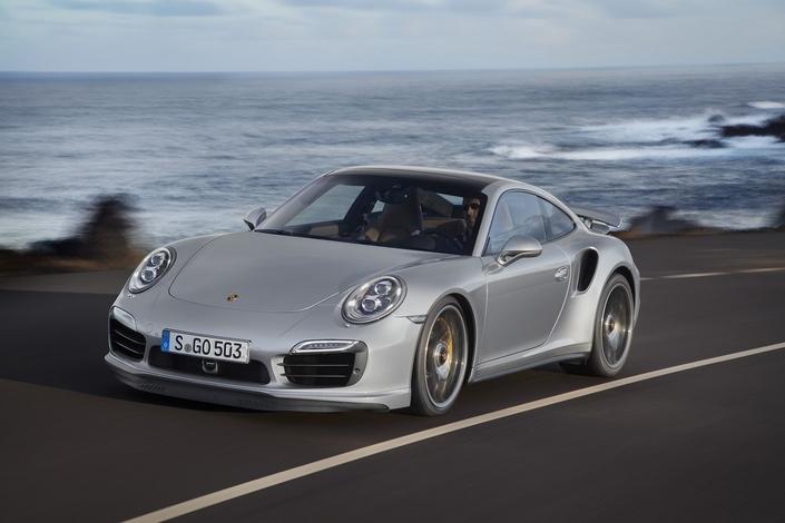 Un chien mâche l'aile de sa Porsche 911 Turbo S