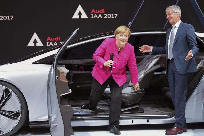 Angela Merkel découvrant le concept-car autonome Aicon sur le stand Audi au salon de Francfort, accompagnée du patron de la marque Ruper Steidler. (photo AFP)