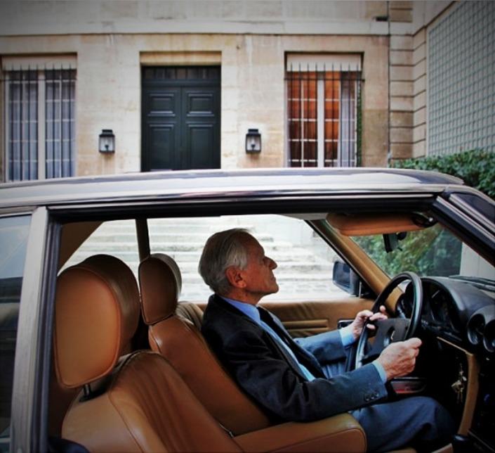 Jean D'Ormesson au volant de sa Mercedes SL, un cabriolet doté d'un hard-top.
