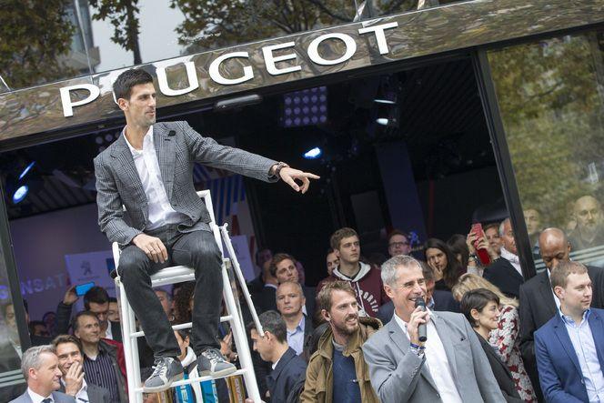 Pour annoncer son partenariat avec l'ATP Tour, Peugeot a organisé des mini-matches ce lundi matin sur le trottoir des Champs-Elysées. Ici, le numéro 1 mondial Novak Djokovic jouant l'arbitre de chaise.