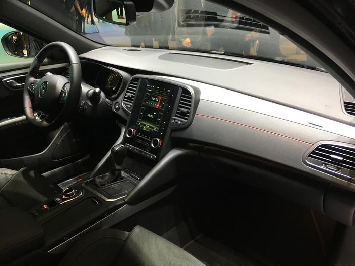 La planche de bord est noire et arbore des inserts aluminium et un cuir noir à surpiqûres rouges. On retrouve ces dernières sur la sellerie, le volant, le soufflet de levier de vitesses et les contre-portes.