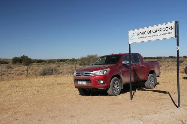 Au cour de sa traversée du désert namibien, le Toyota Hilux pose devant le Tropique du Capricorne.