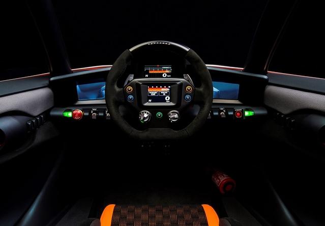 Ambiance mi-sportive mi-futuriste avec ce volant central doté d'un écran et de nombreux boutons.